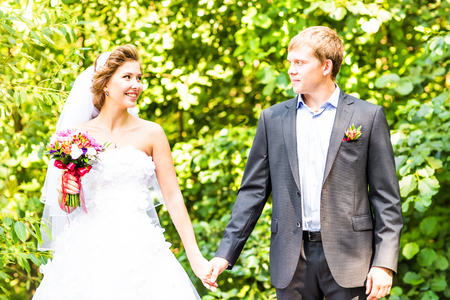 dinner jacket: Bride and groom holding hands outdoors. Wedding, newlywed