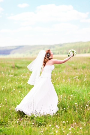 tossing: Bride tossing the bouquet in the meadow Stock Photo