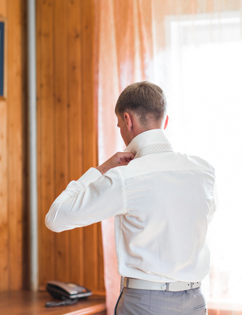 man with work shirt and tie in morning bedroom home.