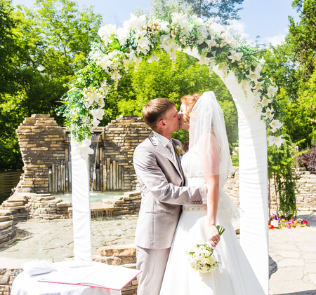 newly married: First kiss of newly married couple under wedding arch.