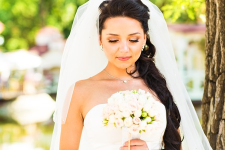 bridal gown: Beauty bride in bridal gown with bouquet and lace veil on the nature. Beautiful model girl in a white wedding dress. Female portrait in the park. Woman with hairstyle. Cute lady outdoors.