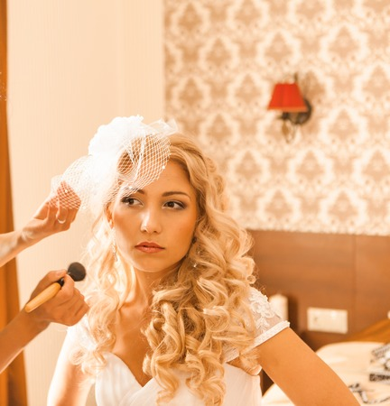 stylist: Stylist makes makeup bride on the wedding day. Stock Photo
