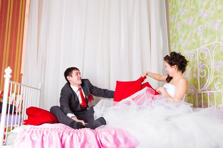 bridegrooms: Portrait of happy newlywed couple fighting with pillows in bed. Stock Photo