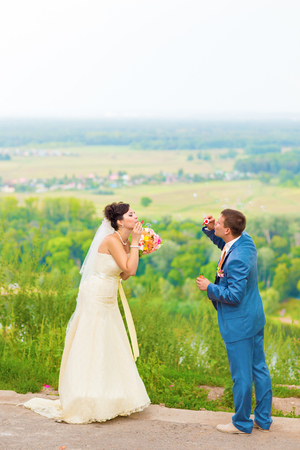 love blow: beautiful wedding couple blowing bubbles in their wedding day