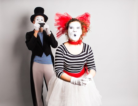 capture the moment: Funny couple of mimes taking a selfie photo on a mobile phone. Concept of  April Fools Day