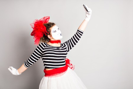 capture the moment: Mime taking a selfie photo. Woman with smartphone. Concept of  April Fools Day Stock Photo