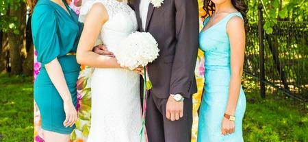 bridesmaids: Handsome groom in suit hugging elegant  bride with bridesmaids.