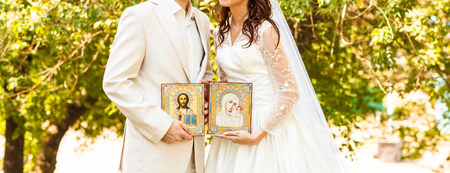 christian altar: Bride and groom after  orthodox wedding ceremony, wedding couple  with icons