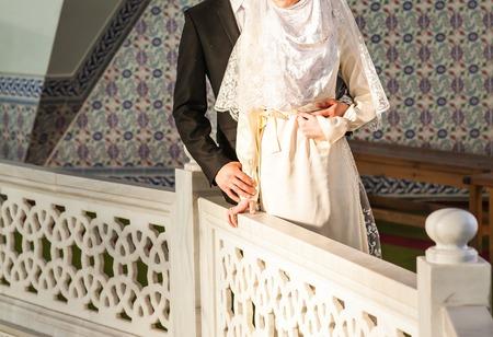 幸せなイスラム教のカップルはモスクの前でポーズします。