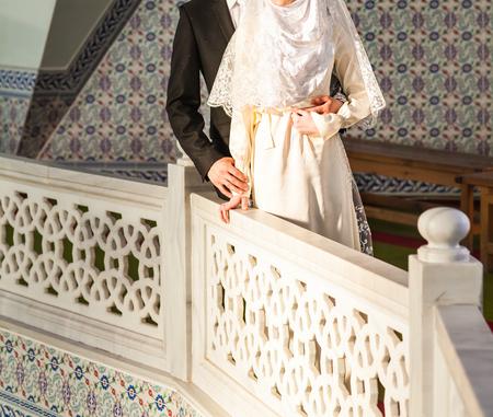 Just married muslim couple posing in front of mosque. Foto de archivo