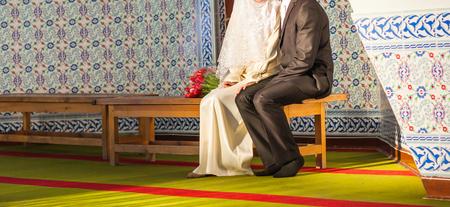 Net getrouwd moslim paar poseren in de voorkant van de moskee.