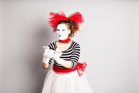 mimo: concepto del Día de los Inocentes. Mime que sostiene el teléfono celular.