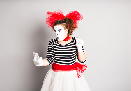mime: April Fools Day concept.  Mime holding cell phone.