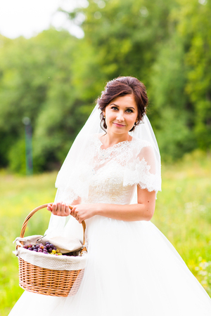 bridal gown: Beauty bride in bridal gown with basket and lace veil on the nature. Beautiful model girl in a white wedding dress. Female portrait in the park. Woman with hairstyle. Cute lady outdoors Stock Photo