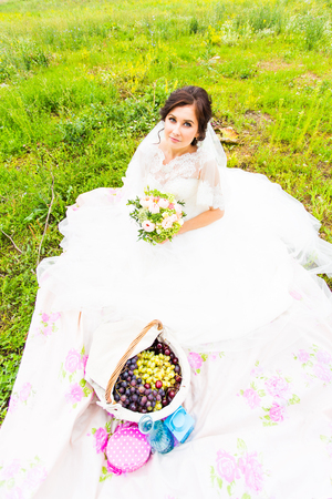 bride sit on a grass with a big basket with fruit.