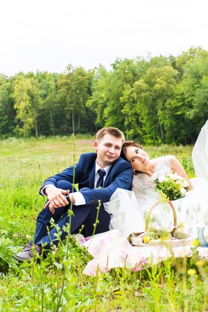 groom and the bride sit on a grass with a big basket with fruit.