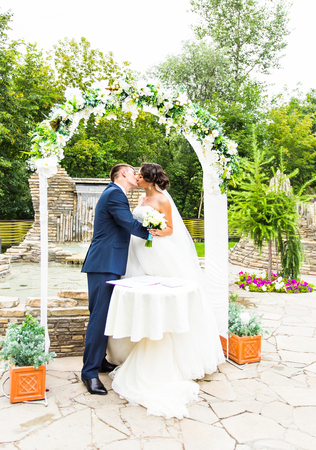 newly married couple: First kiss of newly married couple under wedding arch.