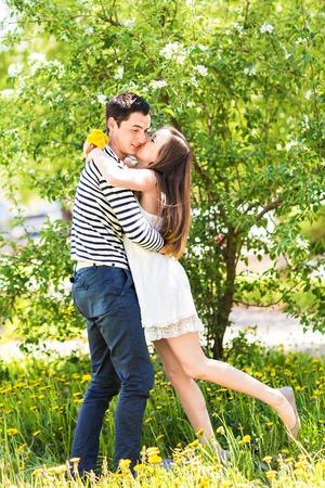 personas besandose: Amantes de la pareja bajo las ramas en flor de primavera día. Hombre adulto joven morena y mujer que se besan en la manzana fresca de flores o árboles de cerezo de jardín. dulce beso. Foto de archivo