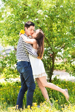hot date: Loving couple under blossoming branches spring day. Young adult  brunette man and woman kissing in fresh blossom apple or cherry trees garden. sweet kiss. Stock Photo