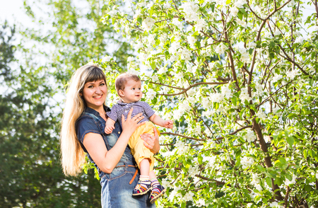 together with long tie: happy loving family with baby son in blooming spring garden. Mother holding baby. Spending time together outdoor. Cozy mood