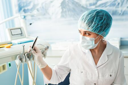 stomatology: people, medicine, stomatology and healthcare concept - happy young female dentist with tools over medical office background. Stock Photo