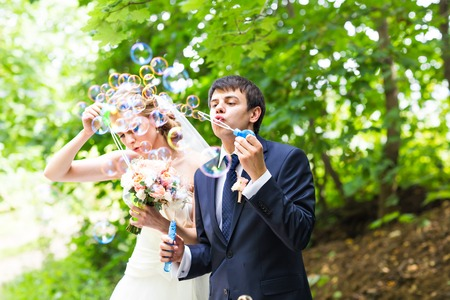 blubber: beautiful wedding couple blowing bubbles. Bride and groom