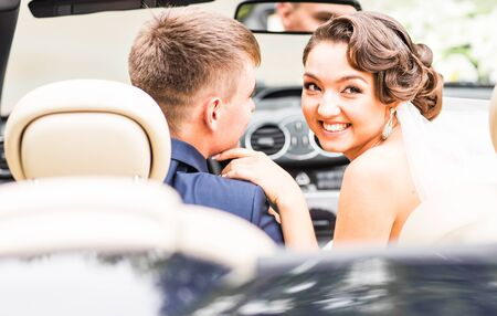 cabriolet: Beautiful young couple bride and groom posing in cabriolet. Stock Photo