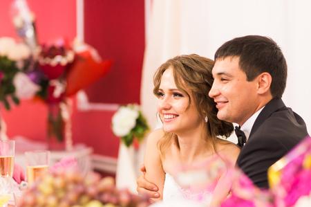 結婚式のテーブルを一緒に座って、手でワインとポーズで新婚夫婦。魅力的な美しい花嫁、優しい目、ターコイズ ブルーのネクタイとスーツに新郎