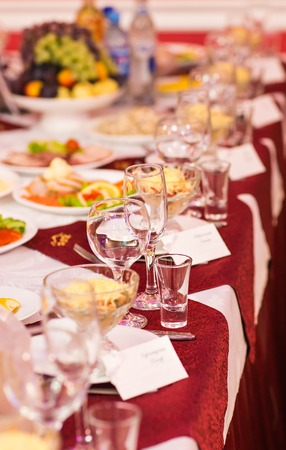 arranging chairs: catering table set service with silverware, napkin and glass at restaurant before party. Stock Photo