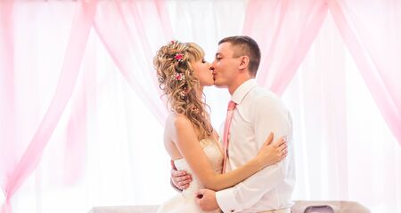 butonniere: Happy bride and groom on their wedding kissing. Stock Photo