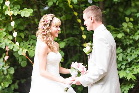 Jonge bruidspaar genieten van romantische momenten buiten op een zomer park. Stockfoto