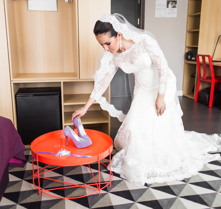 purple shoes: Bride putting on her purple shoes. Wedding preparations