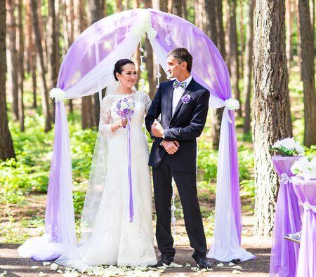 bridegrooms: Bride and Groom Under Archway. Wedding ceremony outdoors