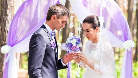 fingers put together: Bride putting a wedding ring on grooms finger. Wedding ceremony.