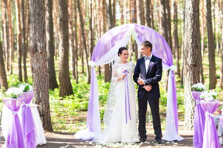 25 30 years women: Bride and Groom Under Archway. Wedding ceremony outdoors
