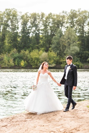Wedding couple walking  near lake.  Bride and groom standing and kissing near lake