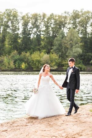 Wedding couple walking  near lake.  Bride and groom standing and kissing near lake