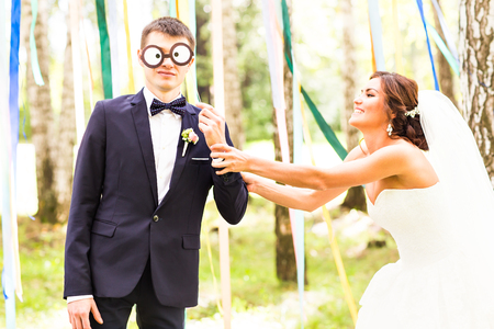 April Fools' Day. Wedding couple have fun with mask Stock Photo