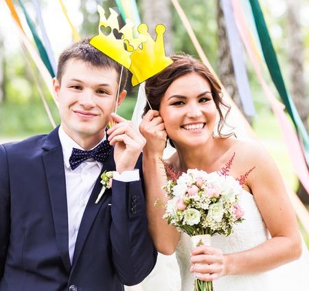 April Fools' Day. Wedding couple posing with crown, mask Foto de archivo