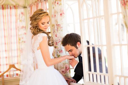 prime adult: Caucasian prime adult male groom kissing hand of female bride.