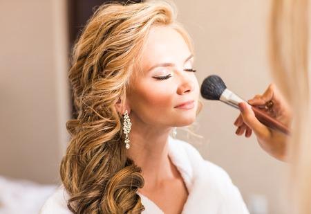 Bruiloft make-up artist het maken van een make-up voor de bruid. Mooi sexy model meisje binnen. Beauty blonde vrouw met krullend haar. Vrouwelijk portret. Bridal ochtend van een leuke dame. Close-up handen in de buurt gezicht