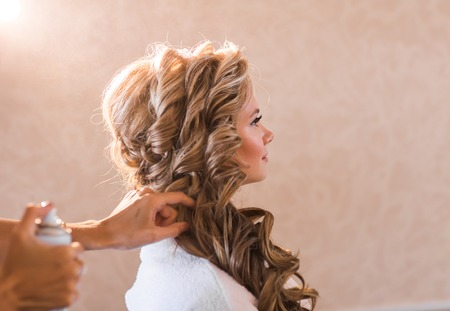 Hochzeit Make-up-Künstler ein Make-up für die Braut zu machen. Schöne sexy Modell Mädchen, das zuhause. Beauty blonde Frau mit dem lockigen Haar. Weibliche Porträt. Brautmorgen von einer netten Dame. Close-up Hände in der Nähe Gesicht