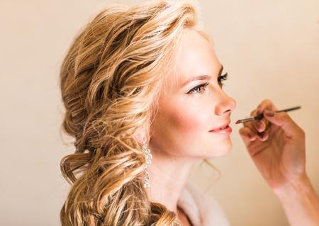 Maquillaje de la boda artista que hace un componer para la novia. Bella modelo muchacha atractiva en el interior. Belleza mujer rubia con el pelo rizado. Retrato femenino. mañana de novia de una señora linda. manos cerca de la cara cerca