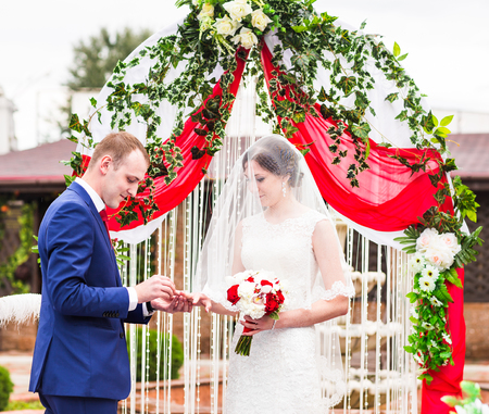 chuppah: Groom putting wedding ring on brides finger. Stock Photo