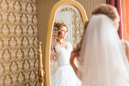 primp: young bride looks at herself in the mirror.