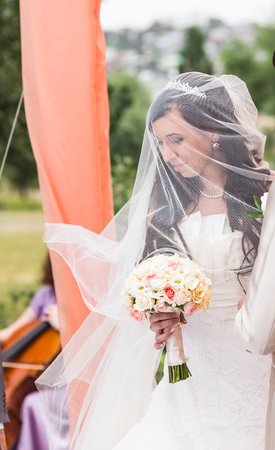 bridal gown: Beauty bride in bridal gown with bouquet and lace veil on the nature. Beautiful model girl in a white wedding dress. Female portrait in the park. Woman with hairstyle. Cute lady outdoors Stock Photo