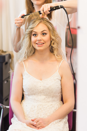 dresser: hair dresser  make hairstyle in beauty salon.