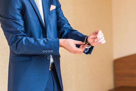 wrist cuffs: Stylish young groom puts on a watch.