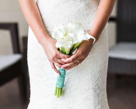 white callas: bride holding a bouquet of white callas. Wedding bouquet