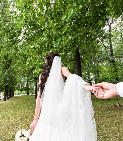 Beautiful young woman bride holds the hand of a man in outdoors. Follow me. Foto de archivo